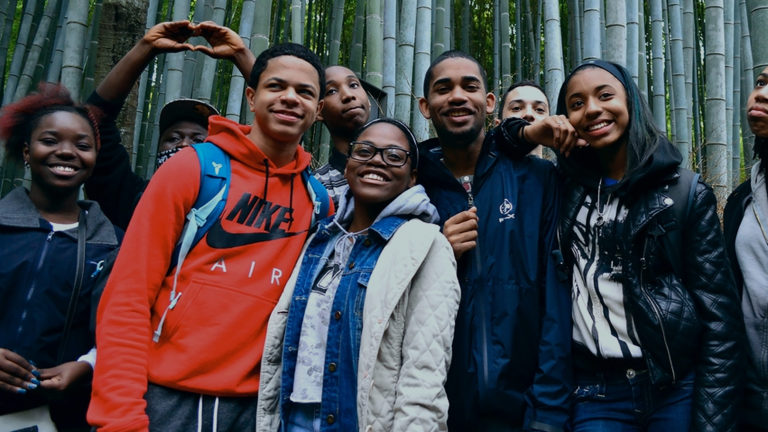 young people posing in front of bamboo trees