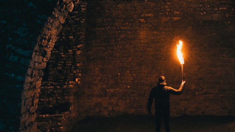 image of man with fire torch surrounded by brick underground tunnel