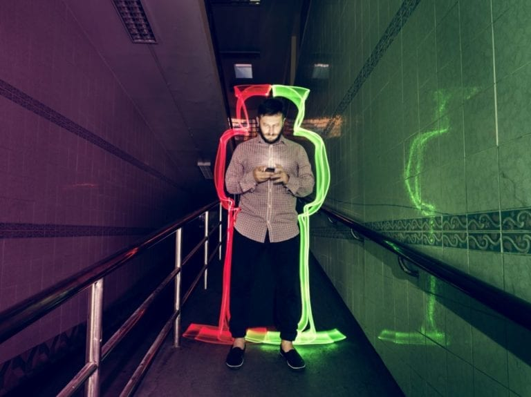 person in corridor surrounded by neon glow