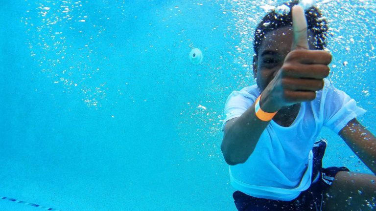 child underwater giving thumbs up