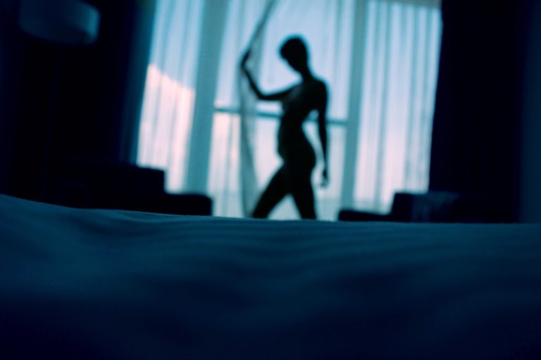 blurred nude person posing in front of window