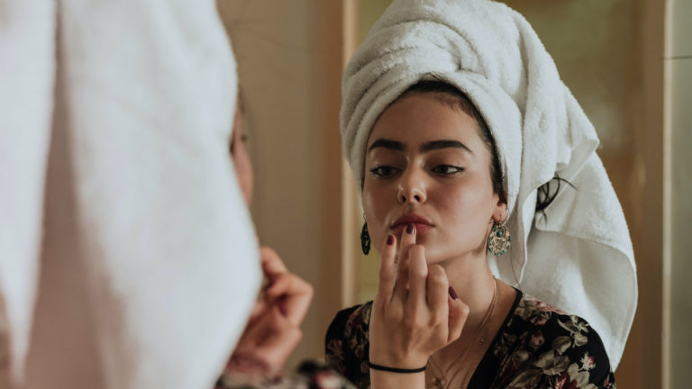 person with towel wrapped around head applying something to their lips in mirror