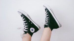 partial calf and foot shot of person wearing black converse