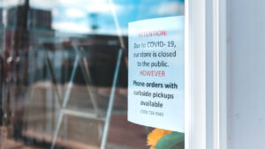 COVID-19 sign in store window showing closed to the public but curbside pickup available