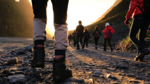 photo of a large group of hikers spread out walking towards a setting sun amongst hills