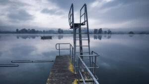 photo of two springboards on a small jetty facing out to the water with land in the distance on a cloudy day
