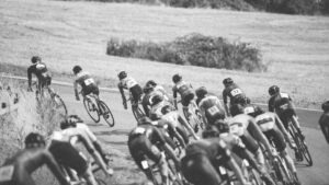 black and white photo of a large group of cyclists in a race going around a bend in the countryside