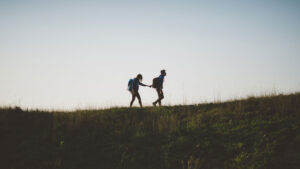 couple wearing backpacks in the middle distance walking a hill against a blue sky and they are holding hands one leading the other