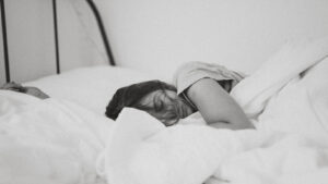 young person in a comfortable looking bed appears to be relaxed and asleep