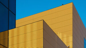 photo of the exterior of a blue and yellow building and a blue sky