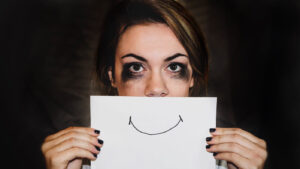 woman with smudged eyeshadow holds a piece of paper with a smiley face on it up in front of her own mouth