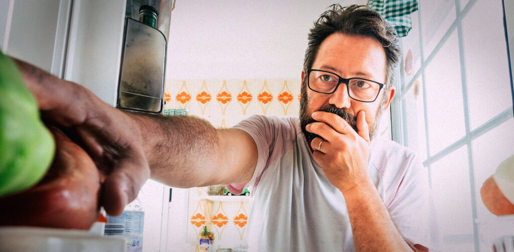 man peering uncertainly into a fridge selecting an apple