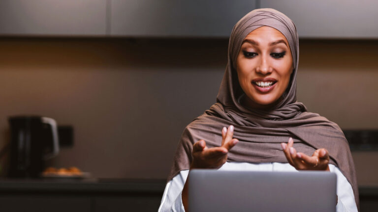 Arab Lady Making Video Call On Laptop Online In Kitchen
