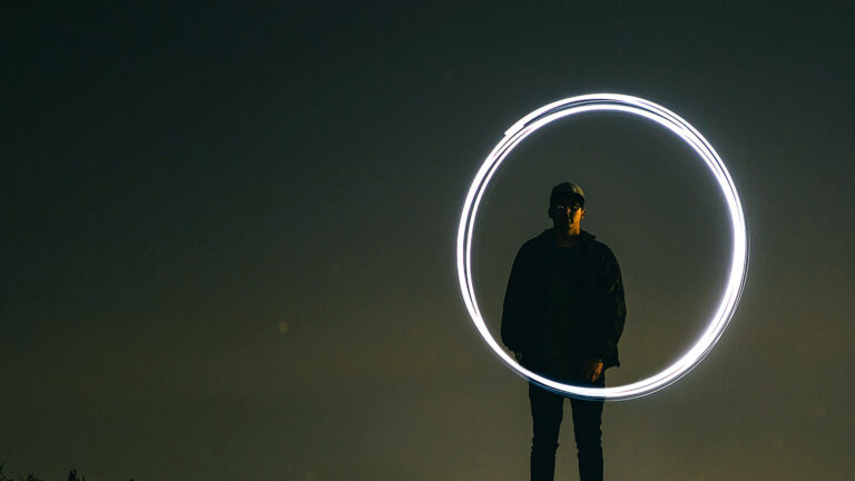 man standing at dusk with circle of light