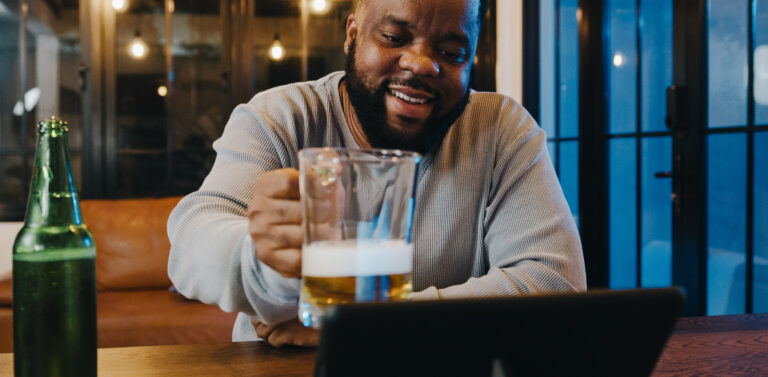 black man raises his beer mug to someone he is having a conversation with on an ipad