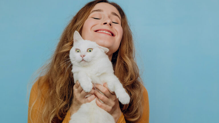 happy person holding up a confused looking cat